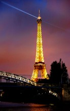 The Eiffel Tower beams a welcome, across the bridge.