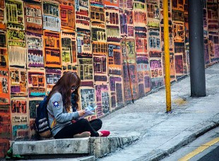 Girl reading by a wall