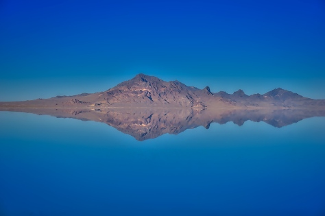 A distant rocky mountain reflects on water covering the Bonneville Salt Flats.